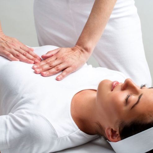 Close up of chiropractor pressing with hands on womans chest at reiki session.